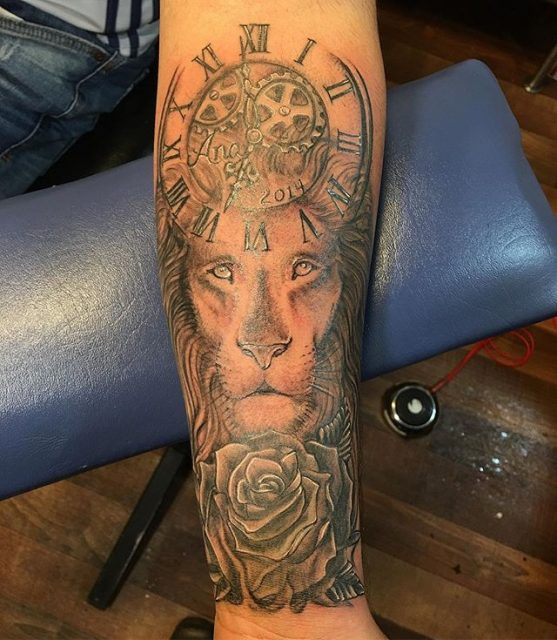 Memorial Lion #shadedtattoo #2sessions #firsttattoo #blackandgrey #rosetattoo #liontattoo #clocktattoo #tattoobliss #carmelny